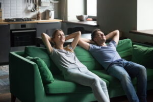 happy-couple-comfortable-on-green-couch-in-living-room