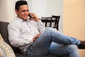 man-sitting-on-couch-talking-on-cell-phone
